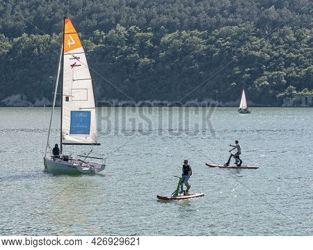 Abrau-durso, Russia - June 13, 2021: Sailing Yachts For Regatta And Men Cycling On Water Bikes