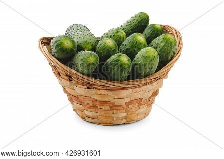 Cucumbers In A Tall Beige Basket Isolated On White.