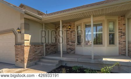 Pano Home Facade With Bay Window Concrete Porch Landscaped Yard And Gabled Garage