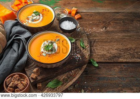 Two Cups Of Pumpkin Soup With Basil And Cream On A Wooden Background. Side View, Space For Copying.