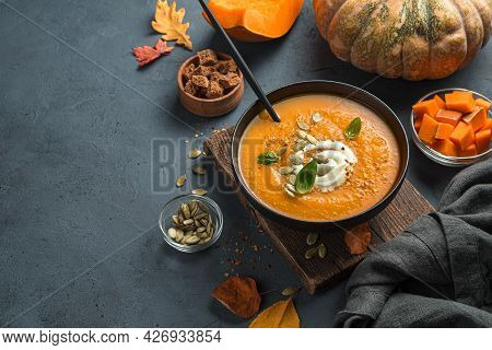 Pumpkin Soup With Cream And Basil On An Autumn Background. Side View, Space For Copying.