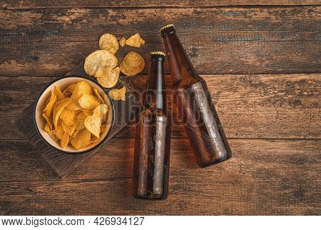 Two Bottles Of Beer And Chips On A Wooden Brown Background. Top View, Copy Space.
