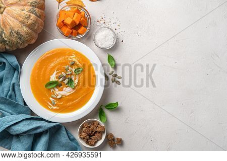 Pumpkin Soup Puree With Cream And Basil On A Gray Background. Top View, Copy Space.