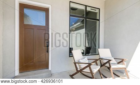 Pano Front Porch With Two Rocking Chairs And Wooden Door With Glass Panel