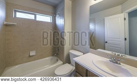 Pano Bathroom Interior With Single Vanity Sink And Bathtub Shower Unit With Ceramic Tiles Surround