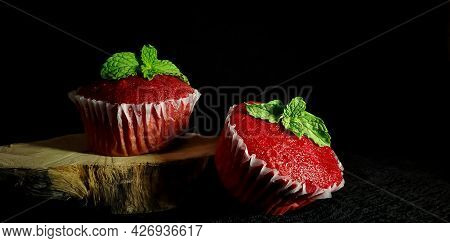Closeup Of Delicious Red Velvet Cupcakes Or Muffins Decorated With Sprinkles And Mint On Top In A Is