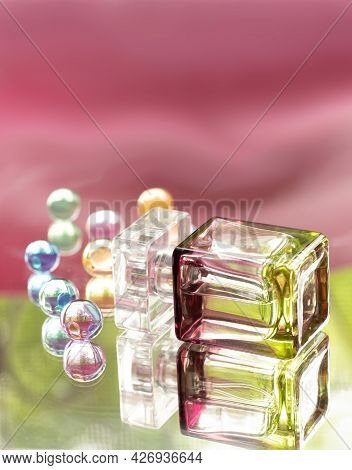 Perfume Bottle With Glass Colored Balls On A Pink Background. Perfumes, Cosmetics, A Collection Of F