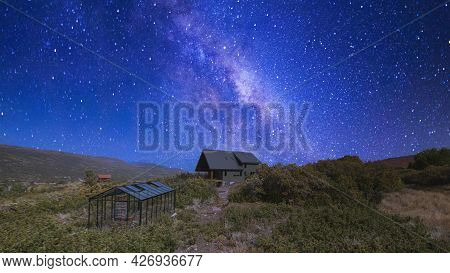 Pano Building Of A House With Glass Greenhouse In The Middle Of A Shrubland Under The Vibrant Night