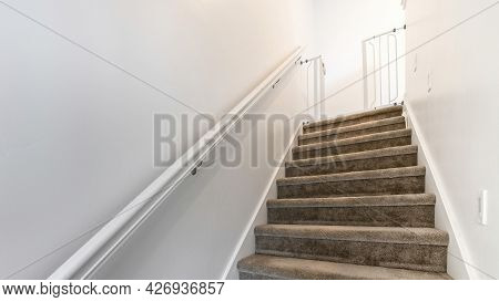 Pano Basement Stairs With Carpeted Steps And Wall Mounted Handrails On A White Wall