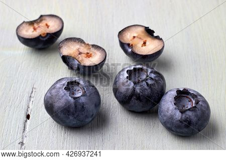 Several Cut Blueberries On A Wooden Blue Background