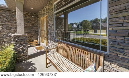 Pano Front Porch Exterior Of A House With Stone Bricks And Wooden Bench