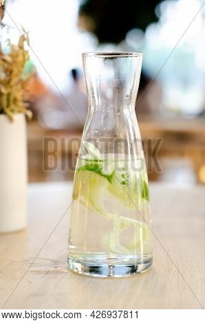 Water With Lemon And Cucumber In A Glass Bottle. Sassy Water For Detox Or Diet On A Wooden Table. He