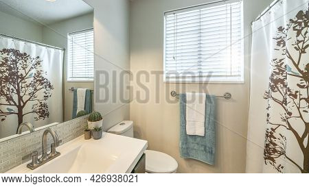 Pano Small Bathroom With Window And Vanity With White Countertop And Integrated Sink