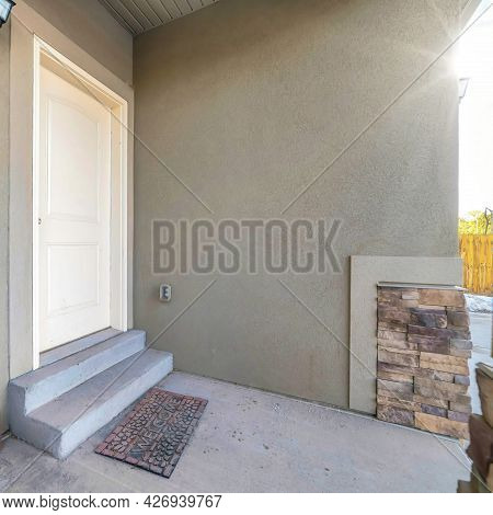 Square Frame White Wooden Front Door With Steps And Doormat At The Entrance Of A Home