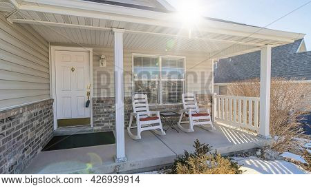 Pano Open Porch Of One Storey House With White Siding And Stone Bricks On Wall