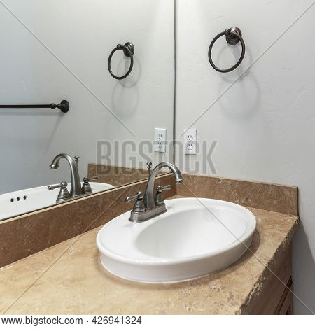 Square Frame Sink With Granite Countertop And A Mirror Inside The Interior Of A Bathroom