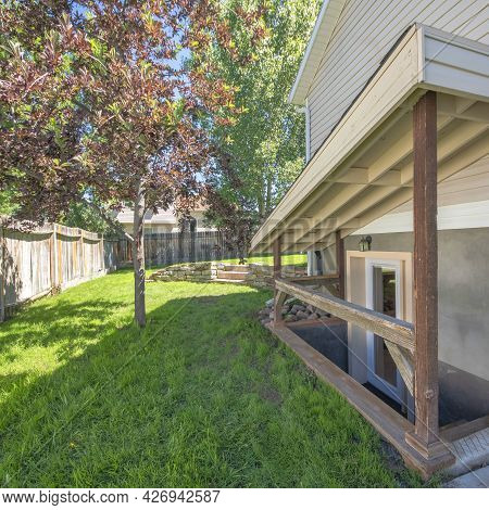 Square Frame Separate Basement Apartment Entrance With Stairs, Glass Panel And Trees On The Lawn At