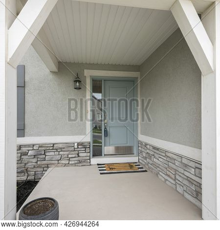 Square Frame Front Porch With Light Gray Door With Side Window Glass Panel, Doormat And Stone Bricks