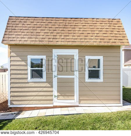 Square Frame Shed At A Backyard With Roof Shingles And Vinyl Wall Siding