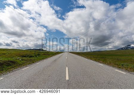 A Low Angle View Of A Paved Highway Leading Straight To The Horizon In A Wild Tundra Landscape