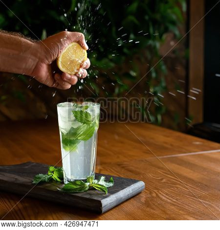 Making Homemade Refreshing Drink. Man Squeezing Lemon Juice Into Glass With Refreshing Healthy Lemon