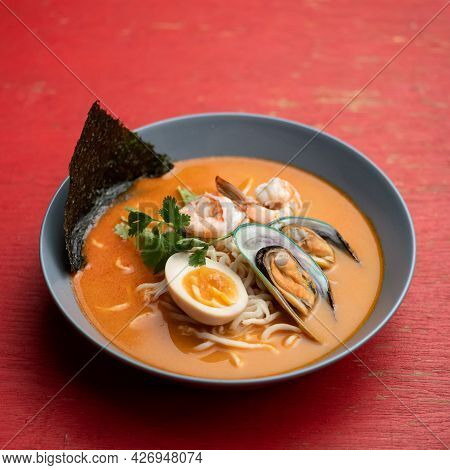 Ramen Soup. Bowl Of Noodles With Shellfish Mussels Or Seafood And Egg On Red Background. Oriental Di