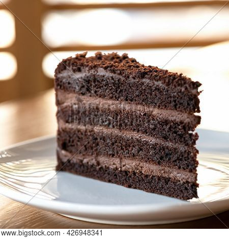 Chocolate Cake. Piece Of Brown Layered Dessert With Cream On White Saucer. Sunny Blurred Background.