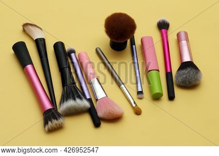 Colorful Beauty Face Makeup Brushes On Yellow Background