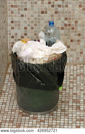 Full Metal Basket Of Trash From Food And Drink Packaging Inside Home Interior