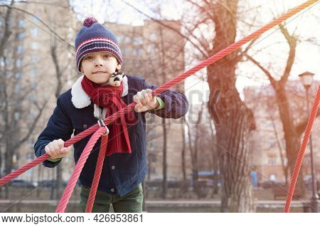 Caucasian Boy Plays On The Playground. A Boy In Winter Clothes Climbs A Rope Town. Spring Or Autumn