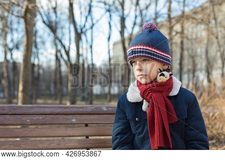 Portrait Of A Caucasian Boy In Winter Clothes In Nature. The Child Is Sad, Sitting On A Bench Alone.