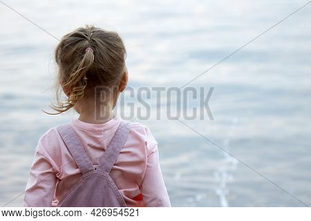 Cute Little Blonde Girl In A Pink Jumpsuit Stands Alone On The Seashore And Throws Pebbles Into The