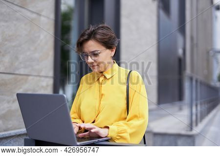 Young Attractive Brunette Businesswoman In Eyeglasses And Yellow Blouse Using A Laptop Near Office B