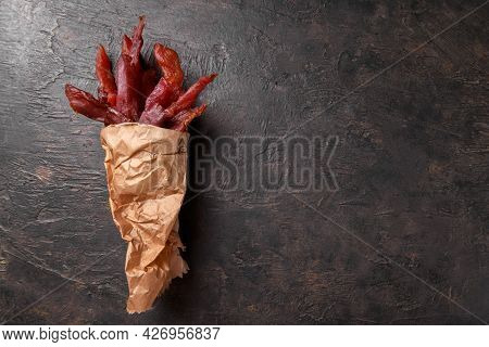 Jerky Meat Strips With Spices And Herbs On A Paper On A Dark Background. Tipical Italian Food Coppie