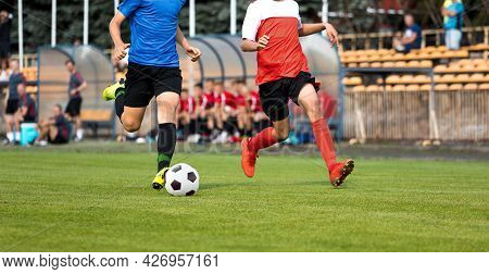 Two Football Players In Running Duel. Soccer Teenage Boys Running Fast With Ball. Players Sitting On