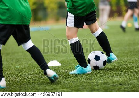 Legs Of Soccer Players Kicking Balls On Training Pitch. Football Soccer Background. Football Practic