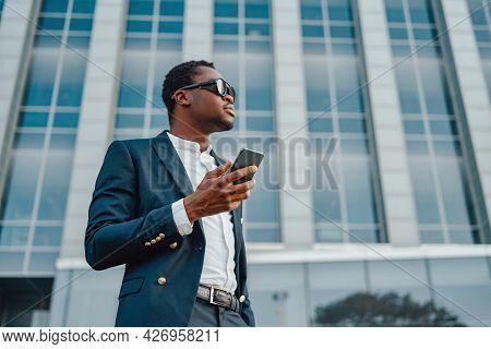 Black Entrepreneur With Smartphone Against City Building