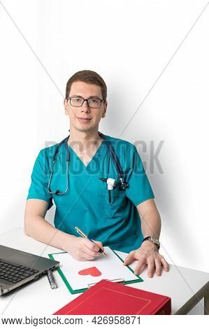 Portrait Of A Doctor Of A Young Man In A Uniform At The Workplace. The Tired Pediatrician Rests And