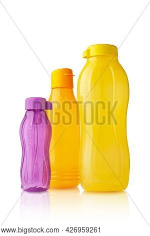 Plastic Tupperware Bottles. Stack Of Plastic Multicolored Drinking Bottles With Ergonomic Cap Isolat