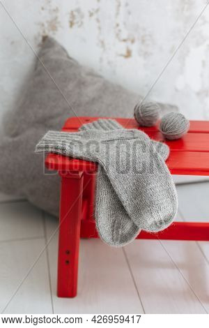 Hand Knitted Socks With Yarn Balls On A Red Stool.  Concept For Handmade And Hygge Slow Life.