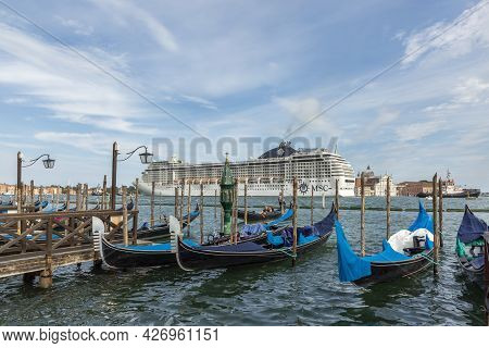 Venice, Italy - July 3, 2021: Cruise Ship Msc Orchestra In The Venetian Lagoon With Gondolas And Tou
