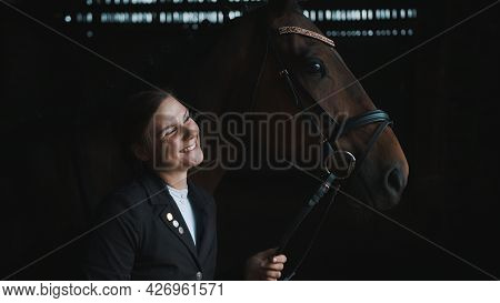 Horsewoman Posing With Her Seal Brown Horse. Smiling And Holding Its Bridle. The Girl Is Dressed In