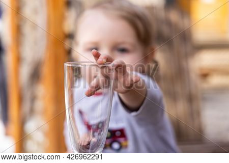 Selective Focus, Blurred Blond Toddler In Background Reaching With His Arm And Hand To Grab An Empty