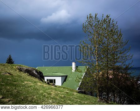 A Scandinavian Style House With Green Roof And Chimney, Hidden Behind Green Hill. Dark, Stormy Sky.