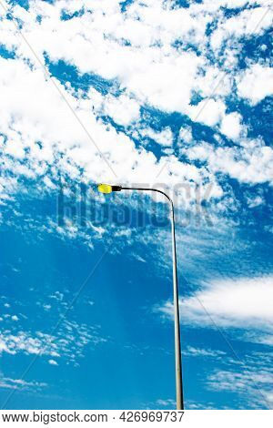Lights On On A Lamppost During The Day. Glowing Lamp Against A Blue Sky With White Clouds.