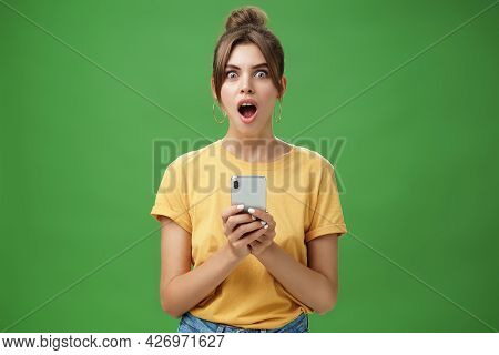 Portrait Of Shocked Speechless And Impressed Beautiful White Girl With Combed Hair In Yellow T-shirt
