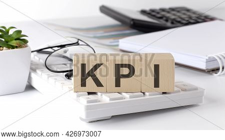 Kpi Written On Wooden Cube On Keyboard With Office Tools