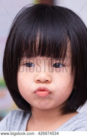 Portrait Of Asian Adorable Girl. Kid Make Wrapping Her Mouth. Head Shot Of Cute Child. Black Short H