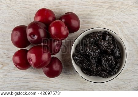 Heap Of Ripe Plums, White Glass Bowl With Prunes On Wooden Table. Top View
