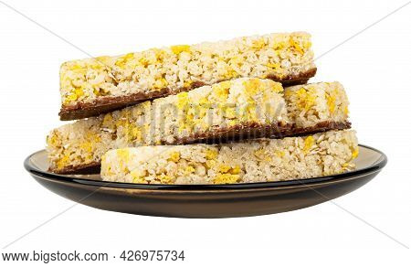 Few Cereal Bars With Coconut And Chocolate In Brown Glass Saucer Isolated On White Background. Side